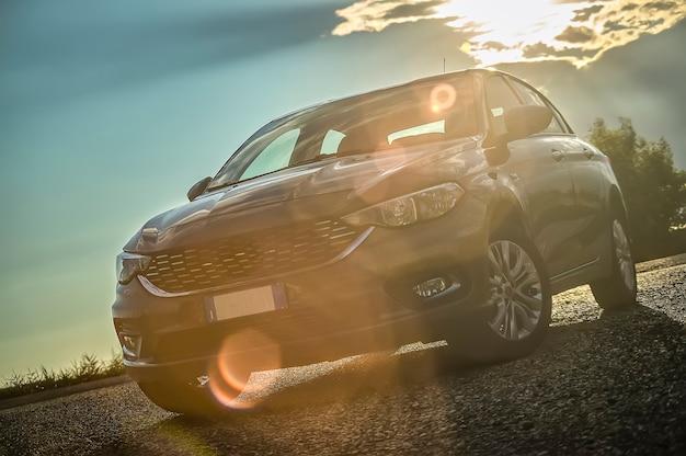 Carro moderno filmado de baixo com grande angular atrás com o pôr do sol e uma bela luz que contrasta. reflexo de luz na lente.