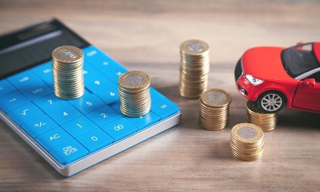 Carro, moedas e calculadora na mesa