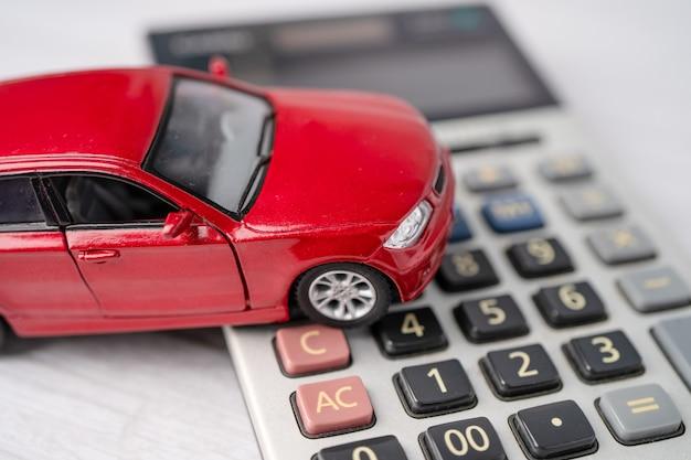 Carro na calculadora, empréstimo de carro, finanças, economia de dinheiro, conceitos de seguro e tempo de leasing.