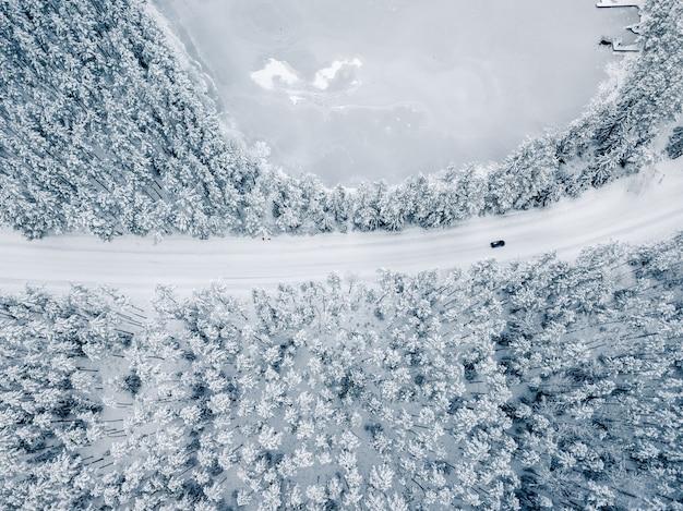 Carro na estrada coberta de neve entre árvores com neve - vista do drone, foto de cima para baixo
