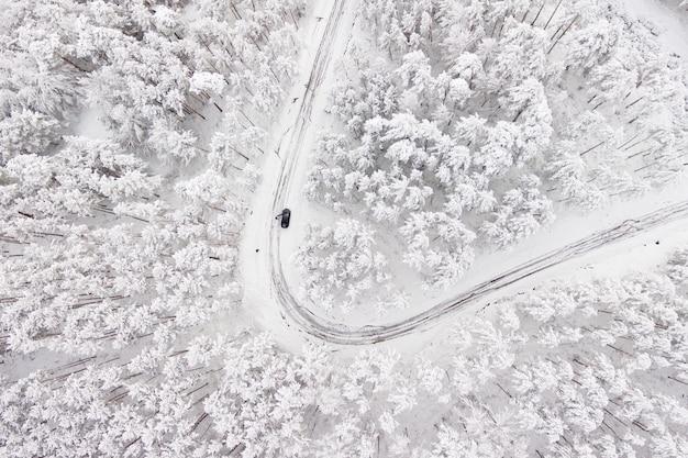 Carro na estrada na calha do inverno uma floresta coberta com a neve. fotografia aérea de uma estrada no inverno através de uma floresta coberta de neve. passagem de alta montanha.