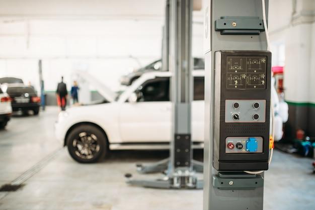 Carro no elevador, interior de serviço em segundo plano. reparação de automóveis, manutenção de veículos