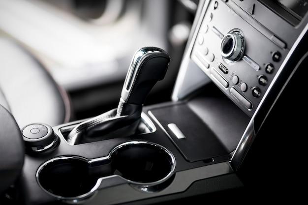 Carro no interior, close-up da transmissão automática, porta-copos e apoio de braço, assentos de couro preto