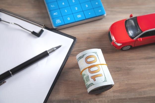 Carro, notas de dólar, calculadora na mesa.