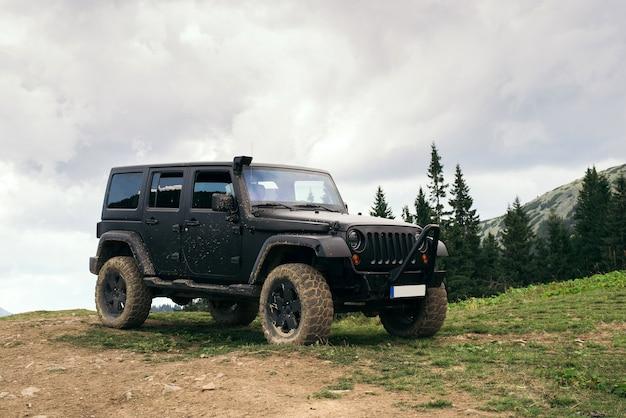 Carro off-road 4x4 enorme no chão sujo nas montanhas no topo.