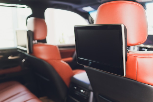 Carro para dentro. interior de carro moderno de prestígio. bancos traseiros com displays, mesas celular.