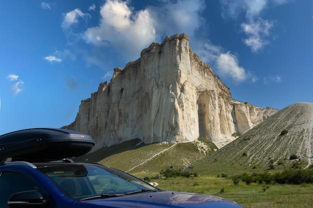 Carro para viajar com rack de teto em uma estrada de montanha, tendo como pano de fundo a pedra branca. foto de alta qualidade