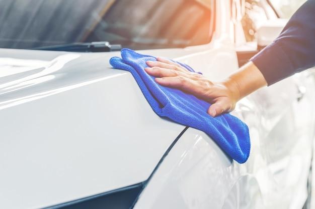 Carro polido trabalhador em uma lavagem de carro