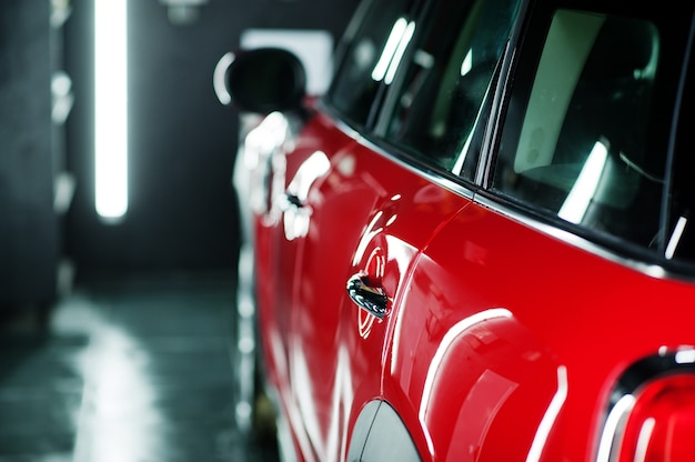 Carro polido vermelho em garagem de detalhamento profissional