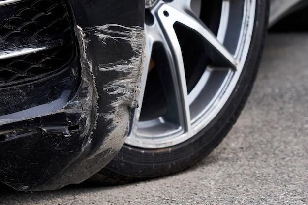 Carro preto arranhado com danos profundos na pintura.