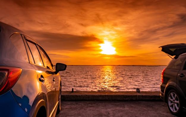 Carro preto e azul suv com esporte e design moderno estacionado na estrada de concreto à beira-mar ao pôr do sol. tecnologia ecológica. viagem de carro de férias.
