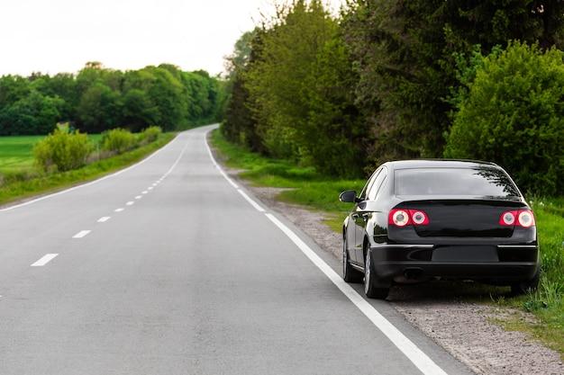 Carro preto em estrada de asfalto