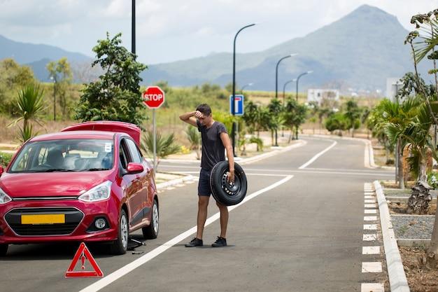 Carro quebrado com roda sobressalente e uma placa no fundo das montanhas