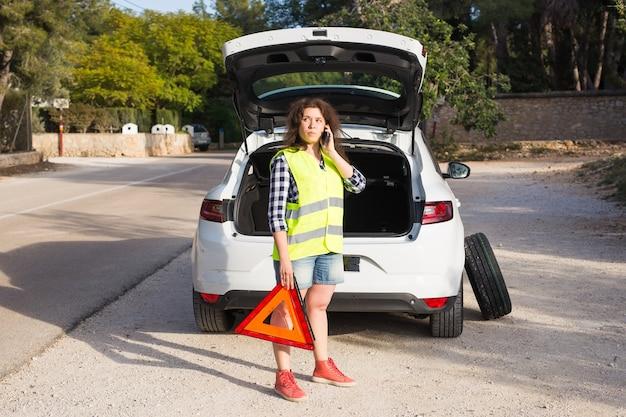 Carro quebrado com triângulo de advertência. mulher parada ao lado de seu carro quebrado na estrada e