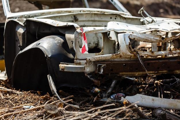 Carro quebrado em uma lixeira no campo