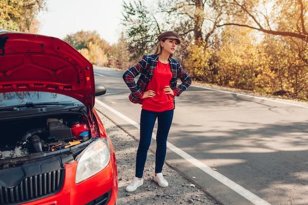 Carro quebrado. mulher triste em pé na estrada por seu automóvel com capô aberto parando automóveis e à espera de ajuda