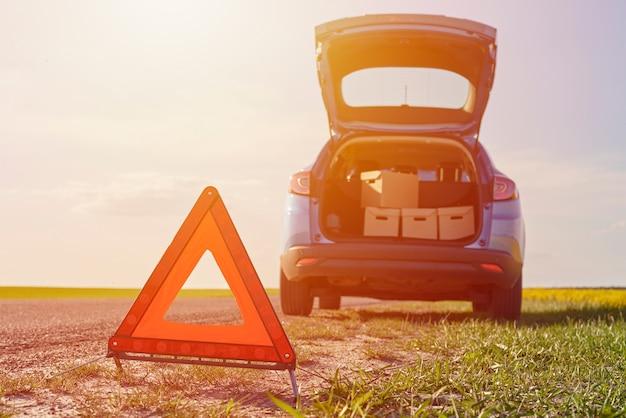 Carro quebrado na estrada e sinal de parada de emergência.