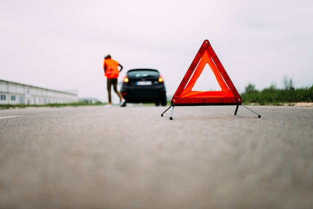 Carro quebrado na estrada. triângulo de aviso vermelho.