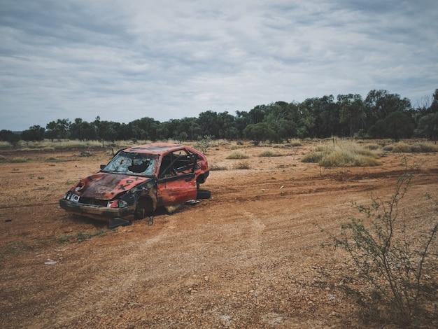 Carro quebrado velho em um campo de grama seca com árvores