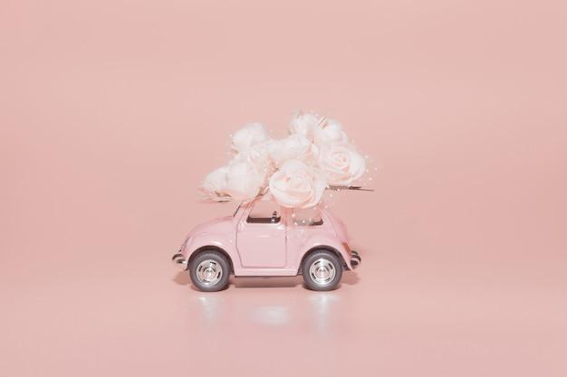 Carro retro cor-de-rosa do brinquedo com o ramalhete das rosas brancas no fundo cor-de-rosa.