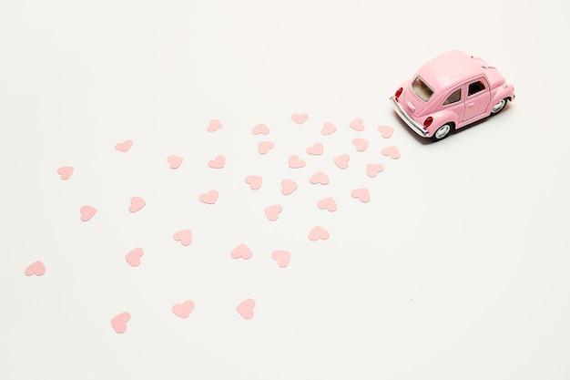 Carro retro cor-de-rosa do brinquedo que entrega corações no fundo cor-de-rosa. cartão de dia dos namorados