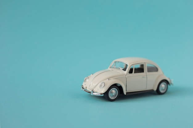 Carro retrô de brinquedo branco em fundo azul