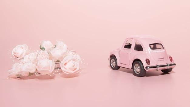 Carro retrô de brinquedo rosa sobre fundo rosa, ao lado de rosas brancas