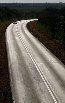 Carro solitário na estrada iluminada pelo pôr do sol