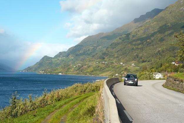 Carro sozinho em uma estrada ensolarada na costa do fiorde