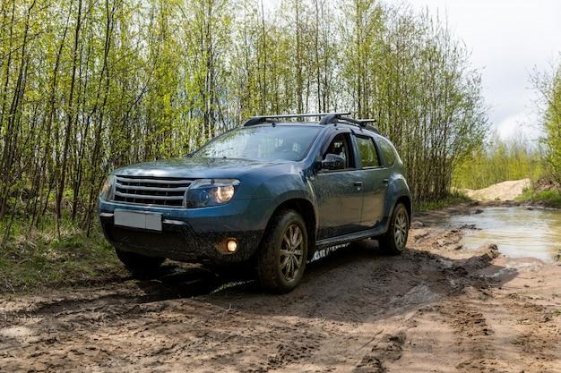 Carro sujo na estrada enlameada em uma floresta.
