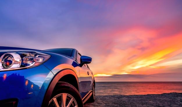 Carro suv compacto azul com esporte e design moderno estacionado na praia ao pôr do sol