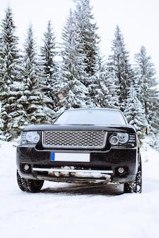 Carro suv em uma cópia da floresta coberta de neve