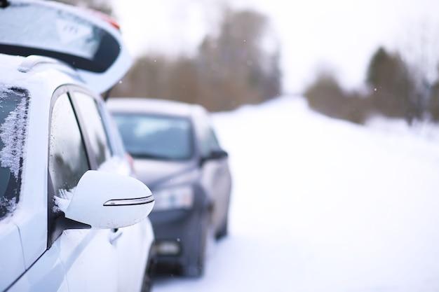 Carro suv moderno fica na beira da estrada da estrada de inverno. viagem em família ao conceito de estância de esqui. aventura de férias de inverno ou primavera. carro na estrada de neve de inverno nas montanhas