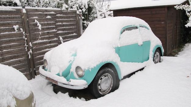 Carro velho coberto de neve dos invernos