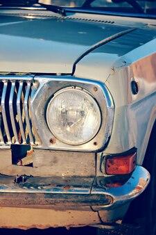 Carro velho do farol redondo dianteiro em condições ruins.