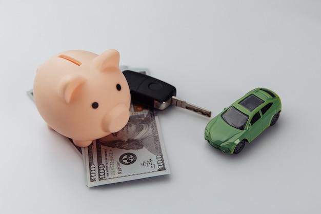 Carro verde com chave, cofrinho e notas de dólar em um fundo branco. poupança e conceito de compras.