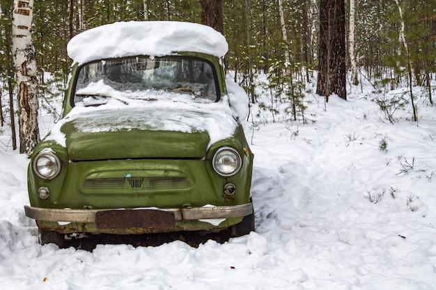 Carro verde retrô fica na floresta de inverno