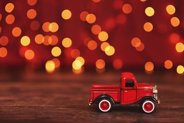 Carro vermelho carregando uma árvore de natal.