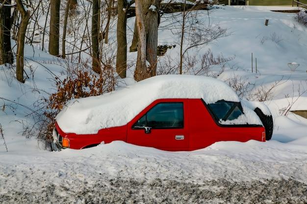 Carro vermelho coberto por uma espessa camada de neve forte nevasca paisagem rural americana de inverno