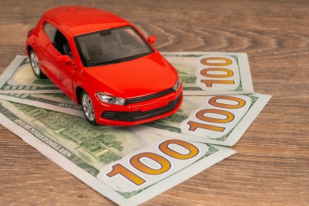 Carro vermelho com notas de dólares, serviço automotivo rico ou conceito de reparo