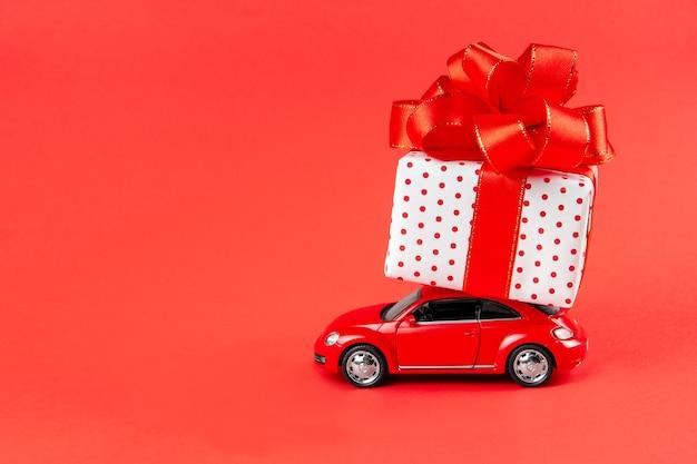 Carro vermelho com presente faz entrega para feriados