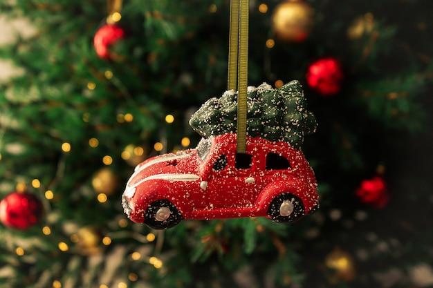 Carro vermelho do brinquedo de natal na árvore do ano novo. composição de natal.