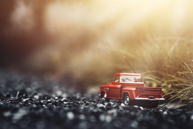 Carro vermelho do brinquedo na estrada ao ar livre no parque no por do sol.