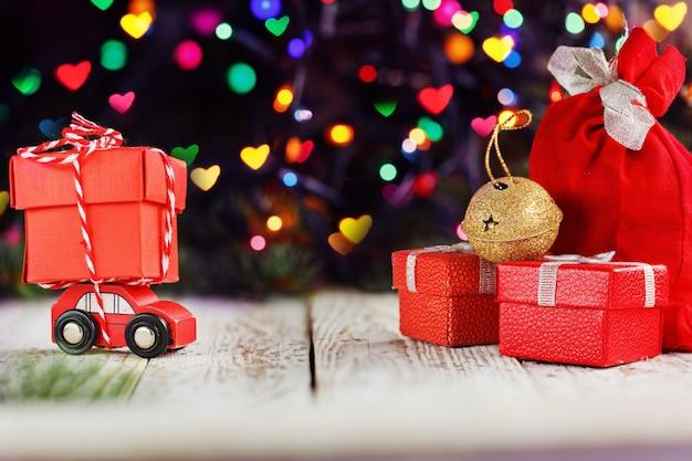 Carro vermelho em miniatura carregando uma grande caixa vermelha. conceito de férias feliz natal.