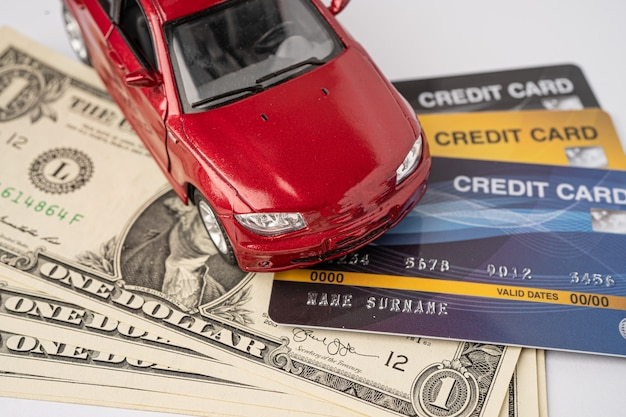 Carro vermelho no cartão de crédito e notas de dólar.