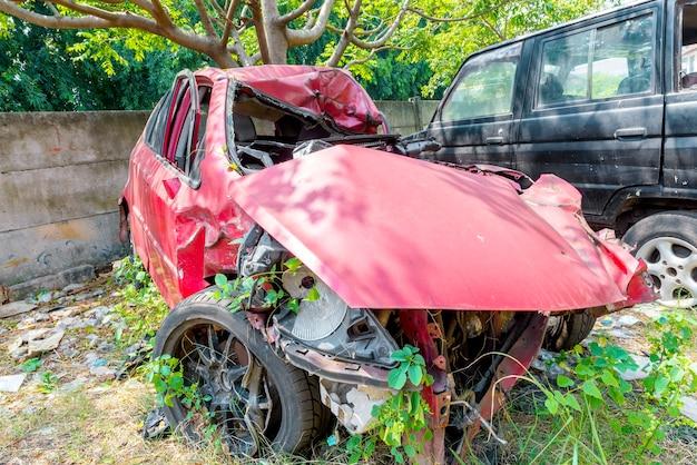 Carro vermelho quebrado por causa do acidente no gramado