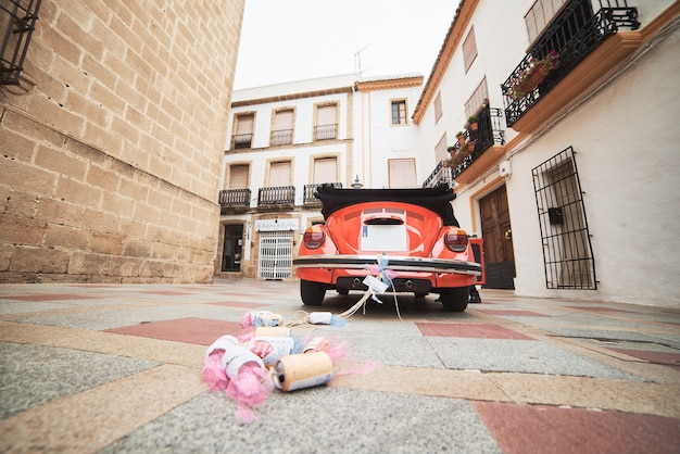 Carro vermelho retro clássico e recém-casados do casamento para dentro.