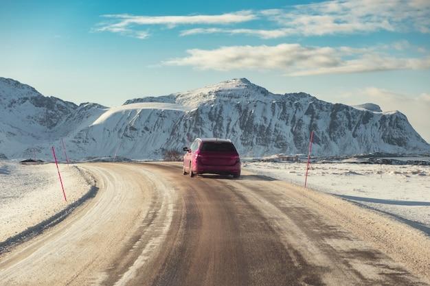 Carro vermelho suv dirigindo na estrada rural com montanha no inverno