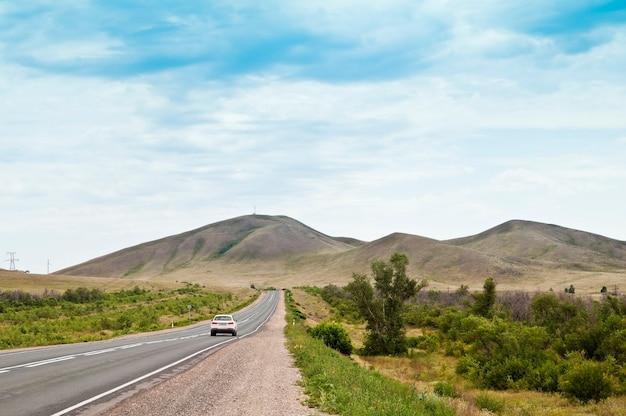 Carro viajando em uma rodovia nas colinas