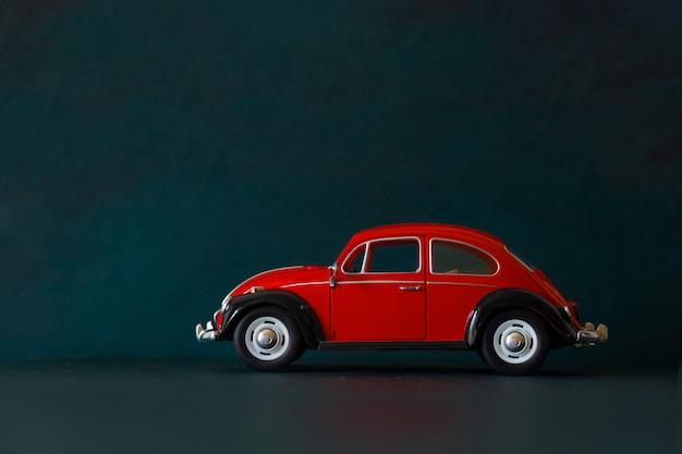 Carro vintage de brinquedo vermelho em fundo escuro